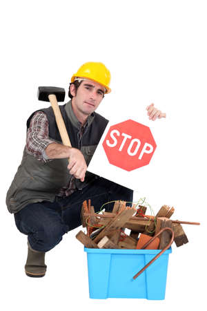Builder kneeling by recycle box Stock Photo