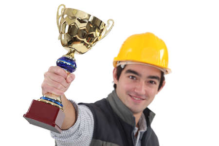 valuable: Young tradesman holding up a trophy