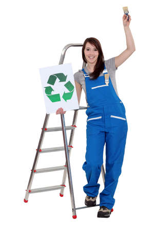 scaling ladder: Woman stood with recycle logo and paint brush Stock Photo