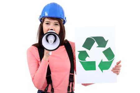 female apprentice shouting in loudspeaker shows recycling logo photo