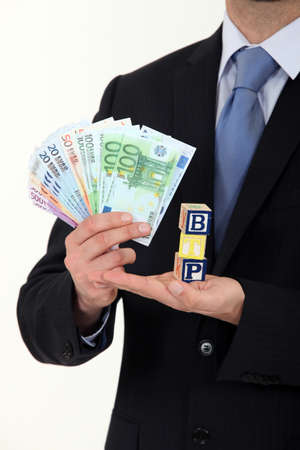 public works: Businessman holding cash and the letters BTP Stock Photo