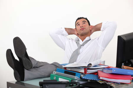 despite: Businessman reclining in his chair despite being overworked