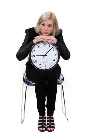 wasting: woman holding a huge clock