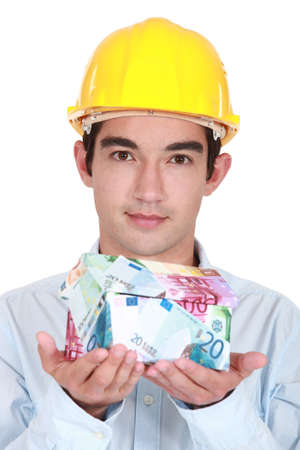 Tradesman holding a house made of money Stock Photo - 16190930