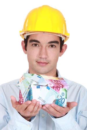 Tradesman holding a house made of money Stock Photo - 16190930