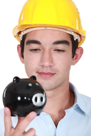 Craftsman looking at piggy bank photo
