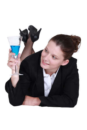 Businesswoman lying down with a cocktail photo