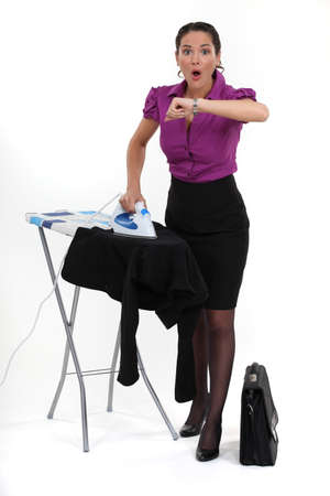 domestic task: Multitasking woman looking at the time Stock Photo