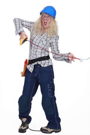 descarga electrica: Electricista Mujer recibiendo un choque Foto de archivo