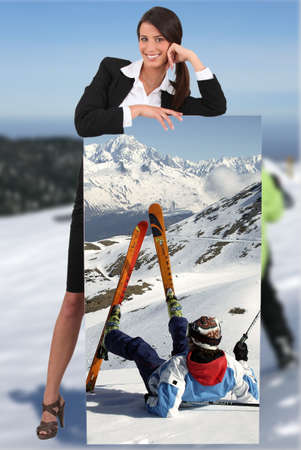 black ski pants: businesswoman at ski leaning on picture of herself printed on canvas Stock Photo
