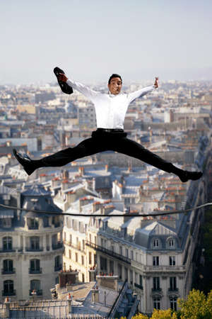 trust people: Businessman jumping for joy on a tightrope