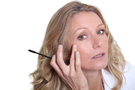 preocupacion: Mujer que aplica el rimel