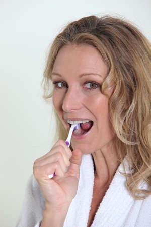 bath gown: Woman brushing teeth Stock Photo