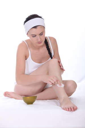 Woman applying beauty product to her legs photo