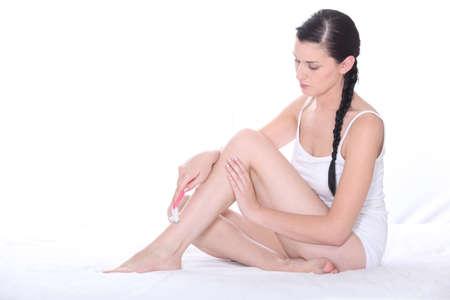 depilacion: Mujer en ropa interior blanca afeitarse las piernas Foto de archivo