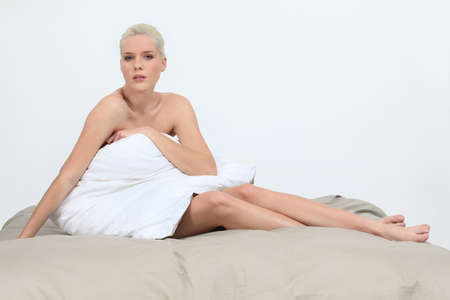 Naked woman sitting on a bed behind a pillow Stock Photo - 16227781