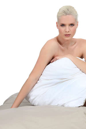 Blonde woman sitting on the bed photo
