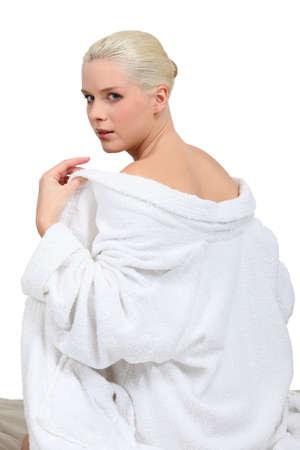 Woman taking off robe photo