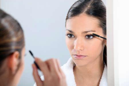 tiedup: Brunette applying eye make-up Stock Photo