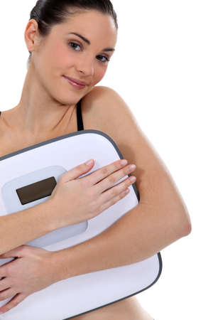 Woman holding bathroom scales photo