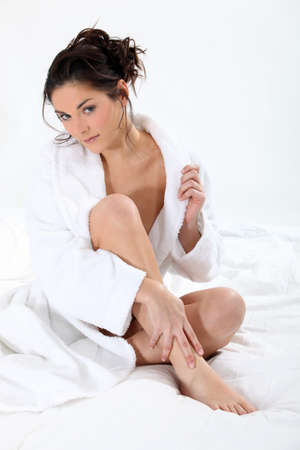 woman in a robe sitting on the bed photo