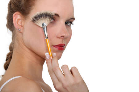 concealing: Woman holding a make-up brush in front of her face