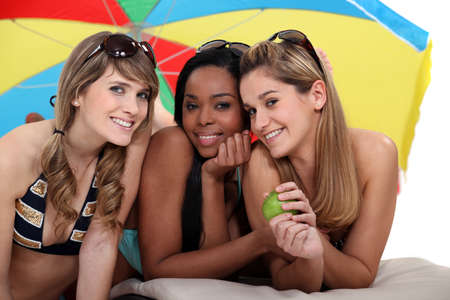 Las mujeres j�venes disfrutando de un d�a en la playa junto Foto de archivo - 16236892
