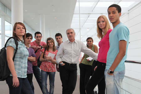 college professor: Group of students and teacher stood in corridor Stock Photo