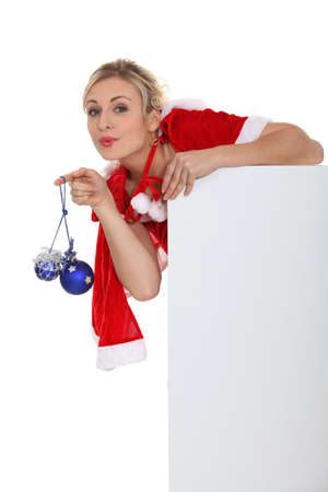 Saucy Miss Santa with baubles and a board left blank for your message Stock Photo - 16227704