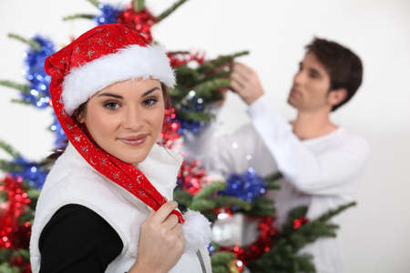 Woman with Christmas cap and man decorating fir photo