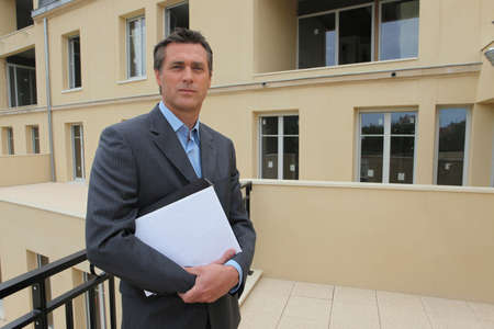 Estate-agent stood outside property