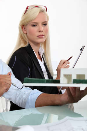 a blonde woman dressed in suit and a man looking a house scale model Stock Photo - 16228048
