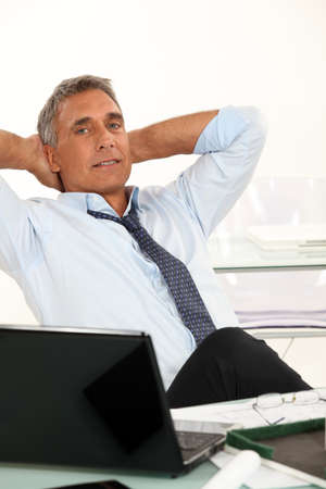 50-55 years old man dressed in shirt and tie is relaxing in his office Stock Photo - 16228028