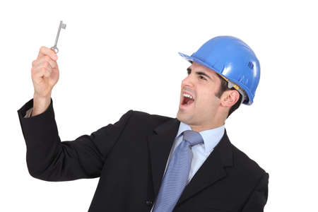 freak out: Delighted businessman in a hardhat with a doorkey