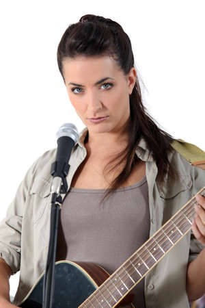 young woman singing and playing guitar photo