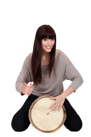 music therapy: Woman banging a bongo Stock Photo