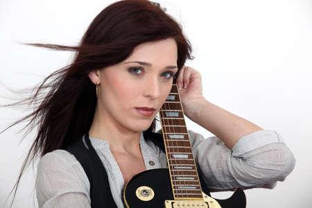 downcast: Serious woman hugging her guitar