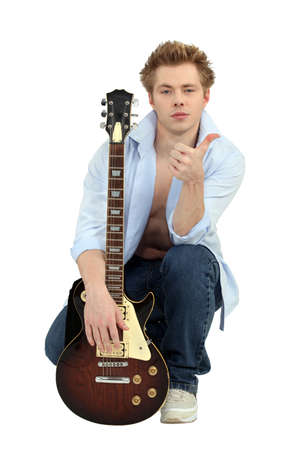 pegheads: Young man posing with his guitar and giving the thumbs up