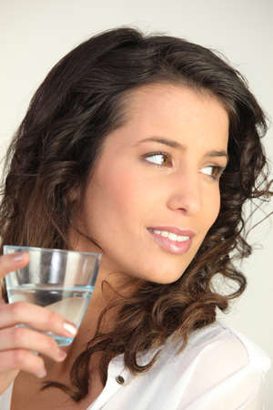 returning: Brunette woman with glass of water