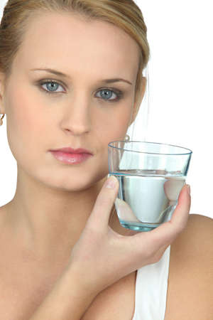 Serious woman with glass of water in hand photo