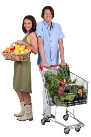 Market vs supermarket: Couple shopping for fruit and vegetables photo