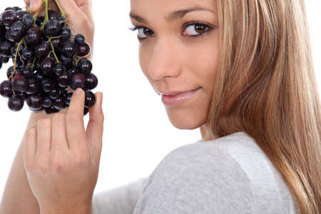 carnal: a young woman savouring sensually a grape