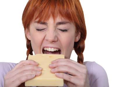 Girl biting piece of cheese photo