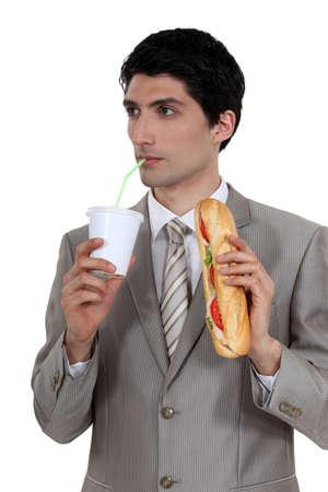 quick snack: smart pensive businessman having quick lunch break