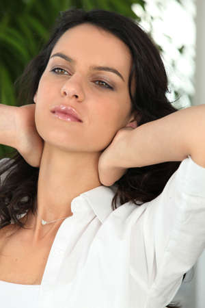 long neck: Woman stretching arms and touching her neck Stock Photo