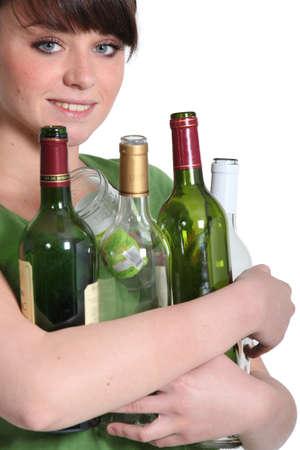 separacion de basura: Chica llevando botellas de vidrio