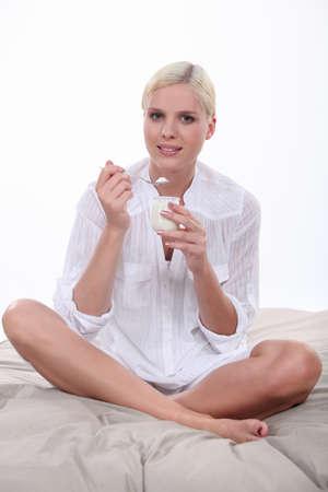 legs folded: Woman eating yoghurt on bed Stock Photo