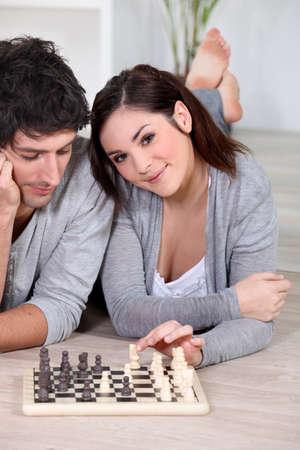 jugando ajedrez: Pareja tirado en el suelo jugando ajedrez Foto de archivo