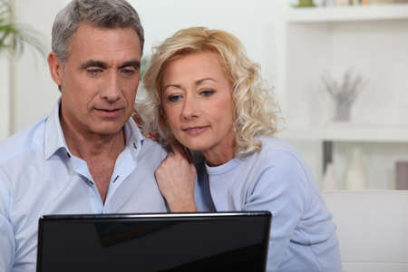 Couple looking at photos on their laptop Stock Photo - 16324231