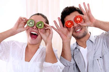Couple holding fruit to their eyes photo